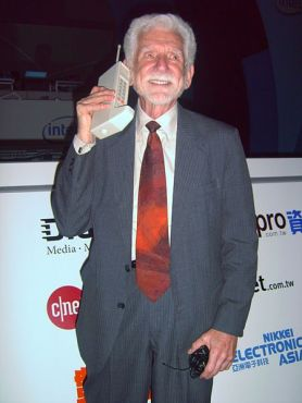 Martin Cooper showing off the first handheld mobile phone, released in 1973.